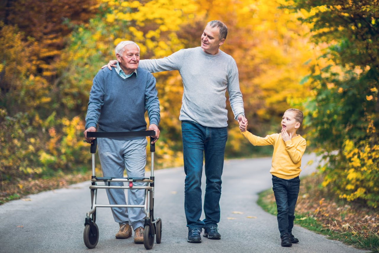 Agape Home senior assisted living allows for more freedom than you think. A grandfather, son and grandson walk down a road in autumn.