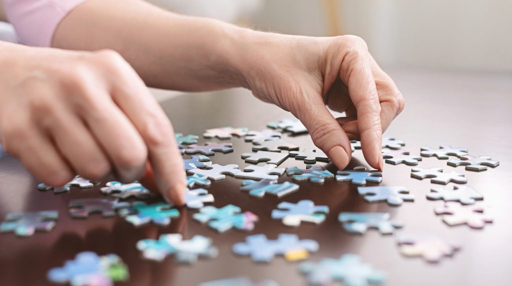 Adult Day Care services means more than a place to stay for hours at a time, DaySpring has a multitude of services that keep older adults engaged. A woman piecing together a puzzle.
