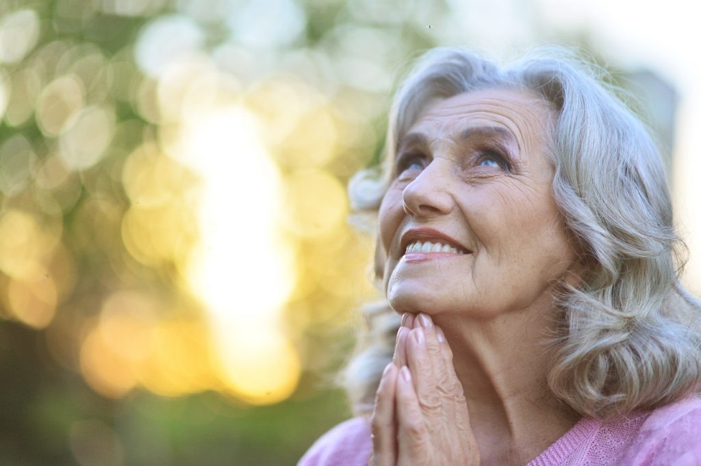 A woman looks to the sky, hands in prayer form. DaySpring Services is one of the leading assisted living facilities in Michigan that shares God's love for seniors.